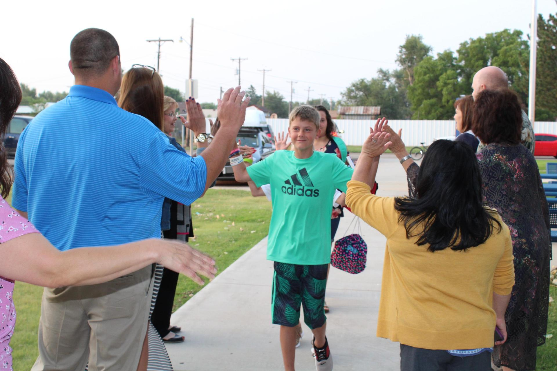 Student walking into the school on the first day greeted by several teachers