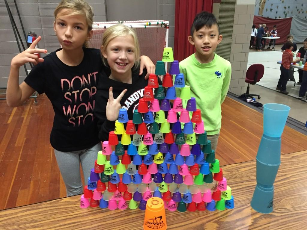 three students show off their cup stacking competition