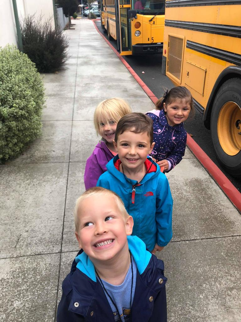 4 children standing and smiling, waiting to get on the school bus