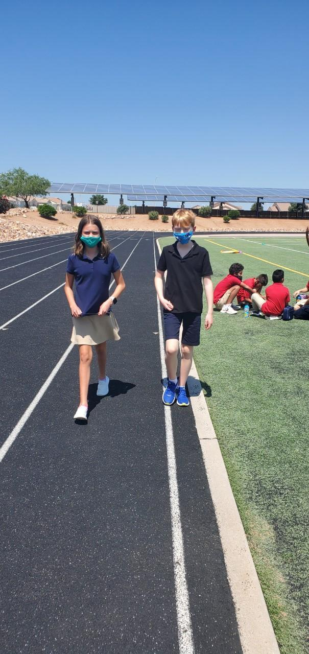 a boy and a girl walking on a track