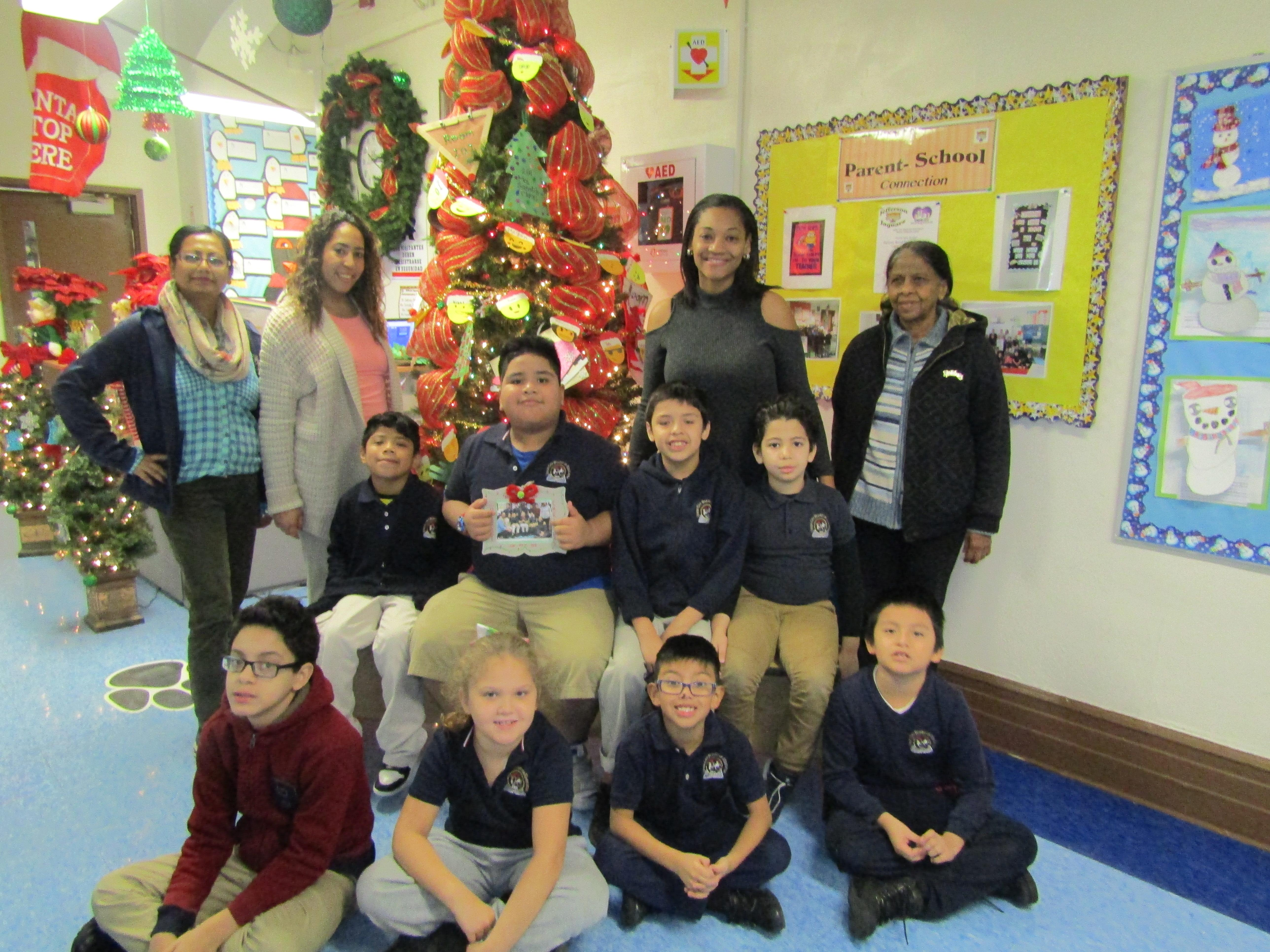 4th grade class with teacher and aide in front of the christmas tree