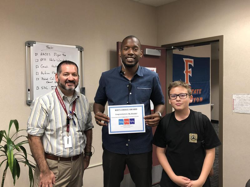 Principal Robert Dominguez, Kristopher Brooks, and Ethan Ulloa smiling at the camera with Mr. Brooks holding a certificate.