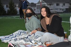 two girls sitting on blanket
