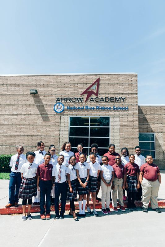 Students posing in front of the school.