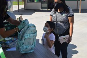 A Shirpser School student gives a thumbs up as she accepts a backpack in her favorite color, one of nearly 550 El Monte City students to receive much-needed back-to-school supplies from L.A. nonprofit Baby2Baby during a special donation event at the school on Sept. 21.