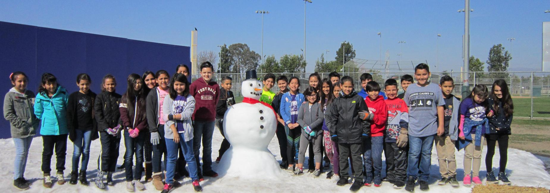 Students stand next to a snow man.