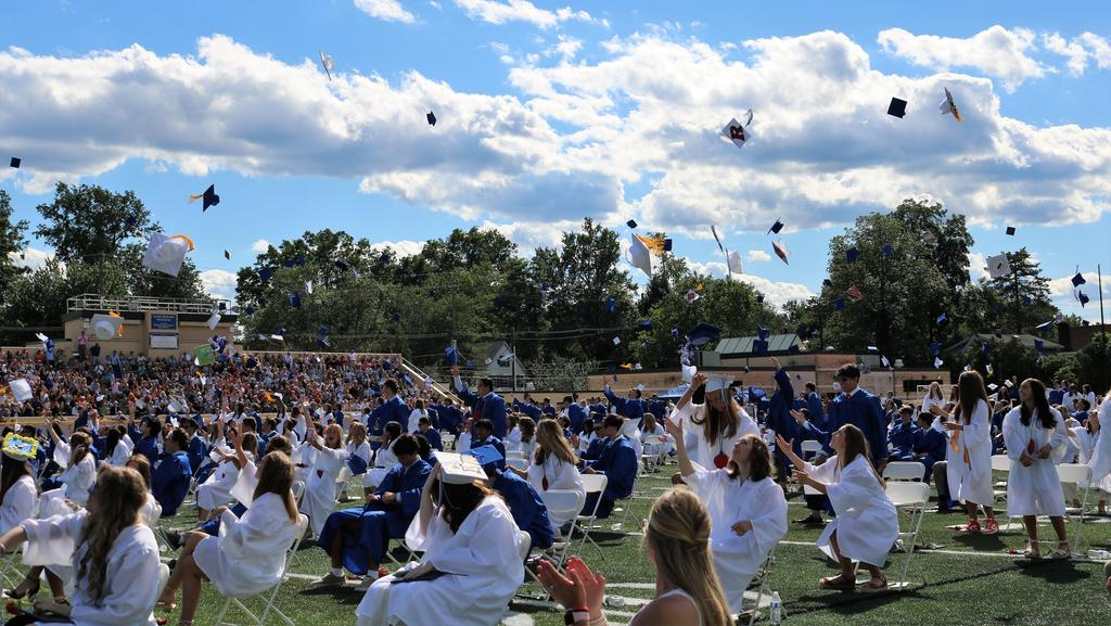 Photo of graduates throwing caps into air