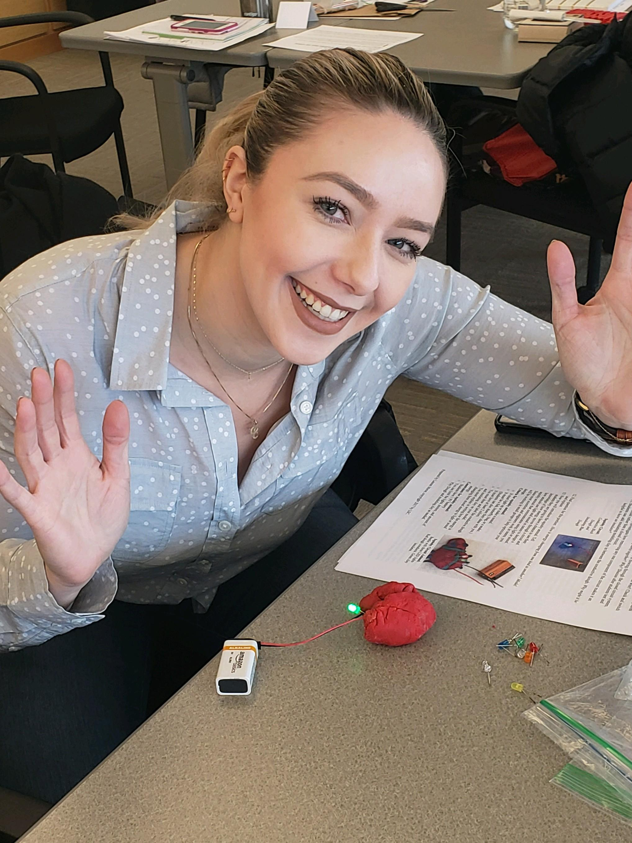 happy teacher with clay brain using a 9v battery to create energy