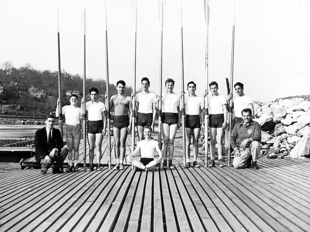 The 1951 crew team posing on the dock with their oars