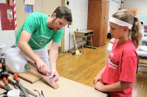 Teacher helps student tune an instrument she built out of recycled materials during STEM Camp.