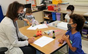 Photo of teacher working with kindergartner