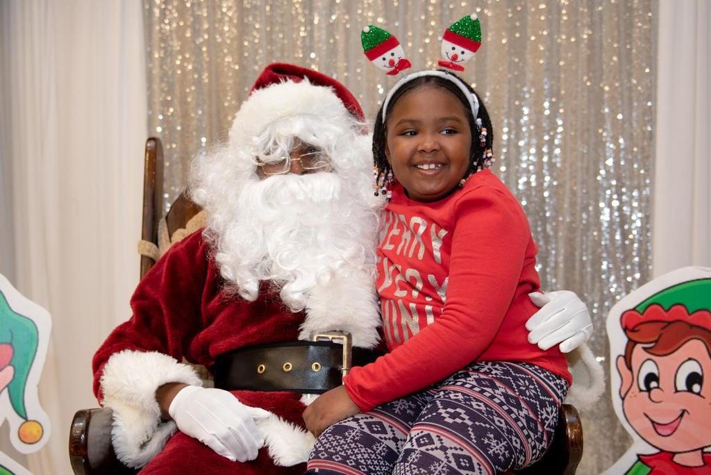 A smiling girl visits with Santa