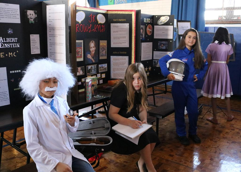"Photo of four 5th graders dressed as famous persons during annual ""Wax Museum"" event."