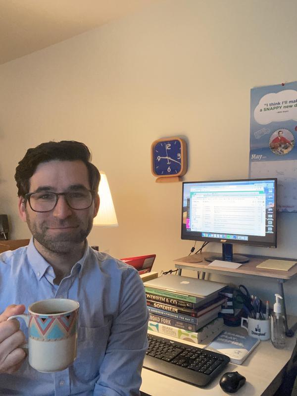 Teacher with a coffee mug sitting at wfh desk