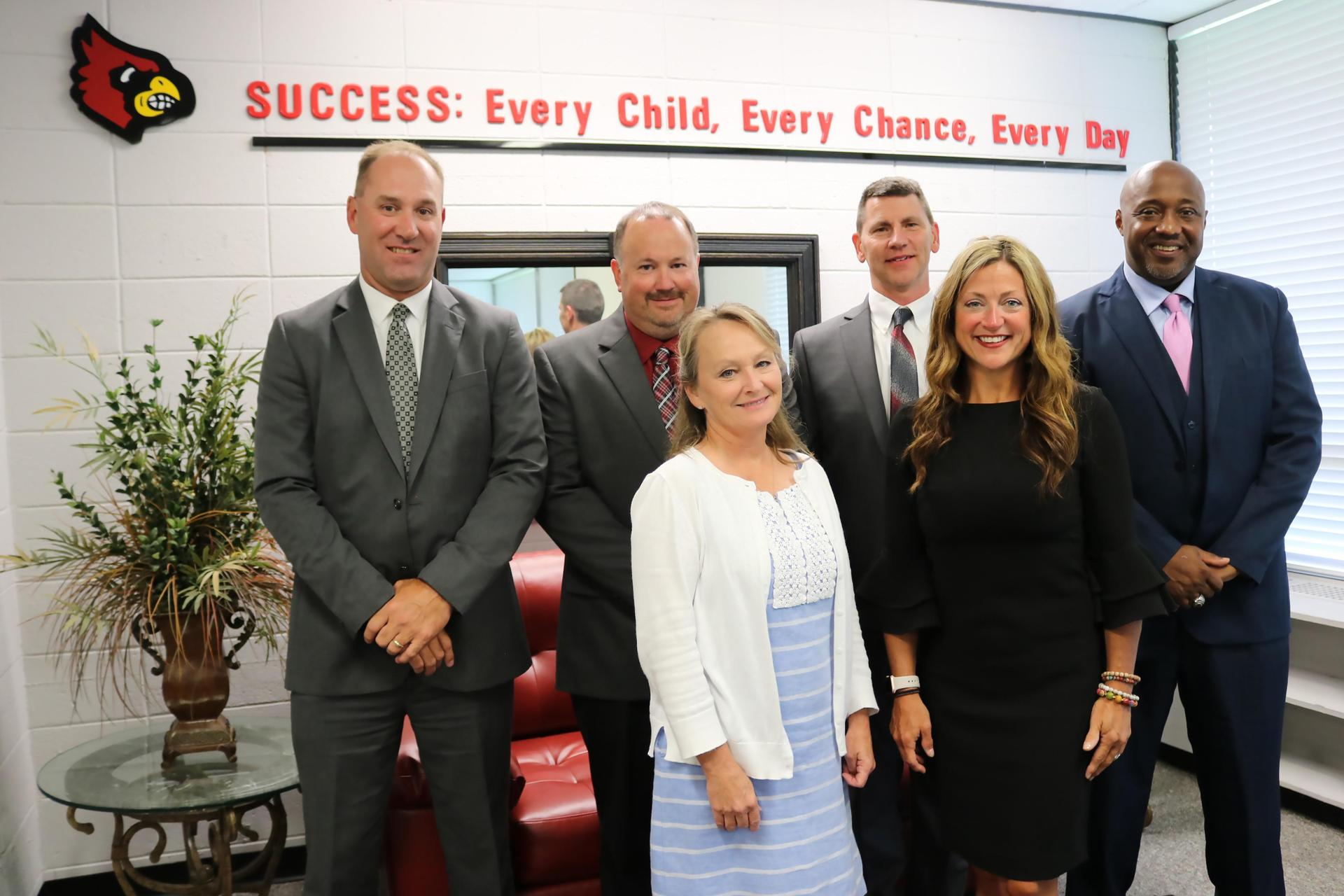 Picture of all Board Members standing in front of district moto 'Success: Every Child, Every Chance, Every Day'