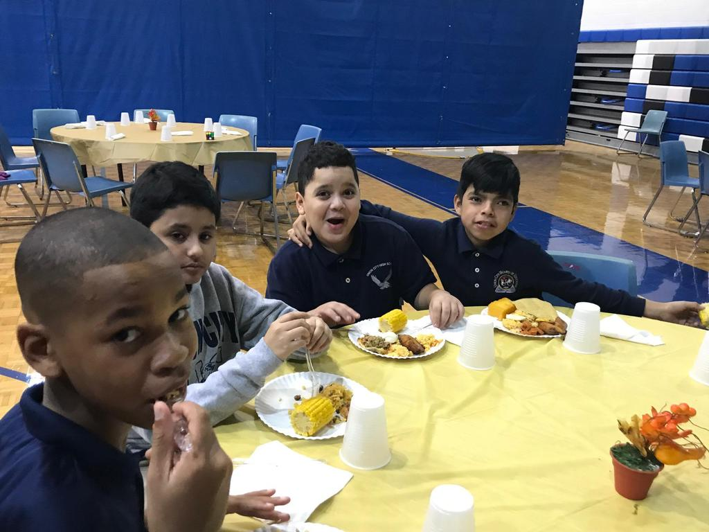 four boys seated together at a table enjoying a good meal