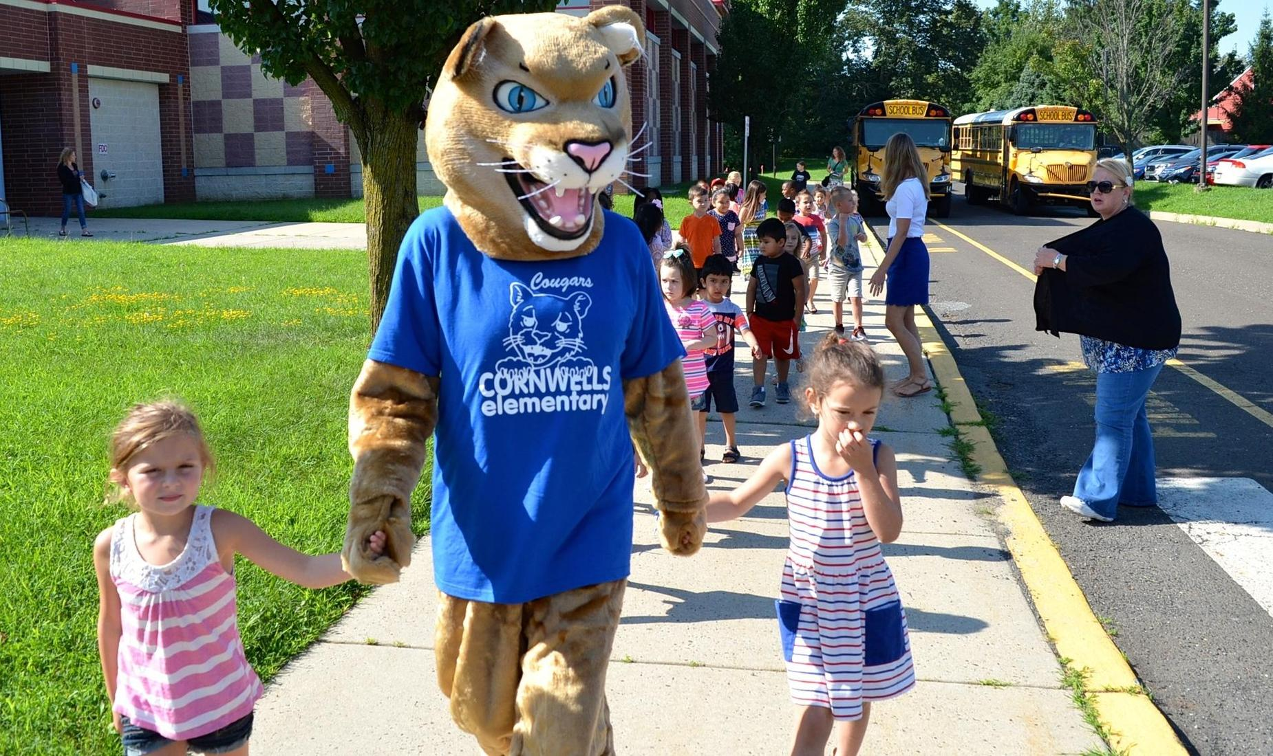Cornwells Elementary mascot, the Cougar, holds hands with two girls and leads the others into school.