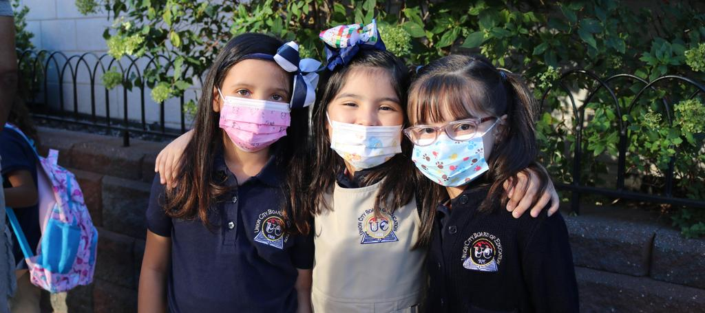3 girls wearing masks smiling outside