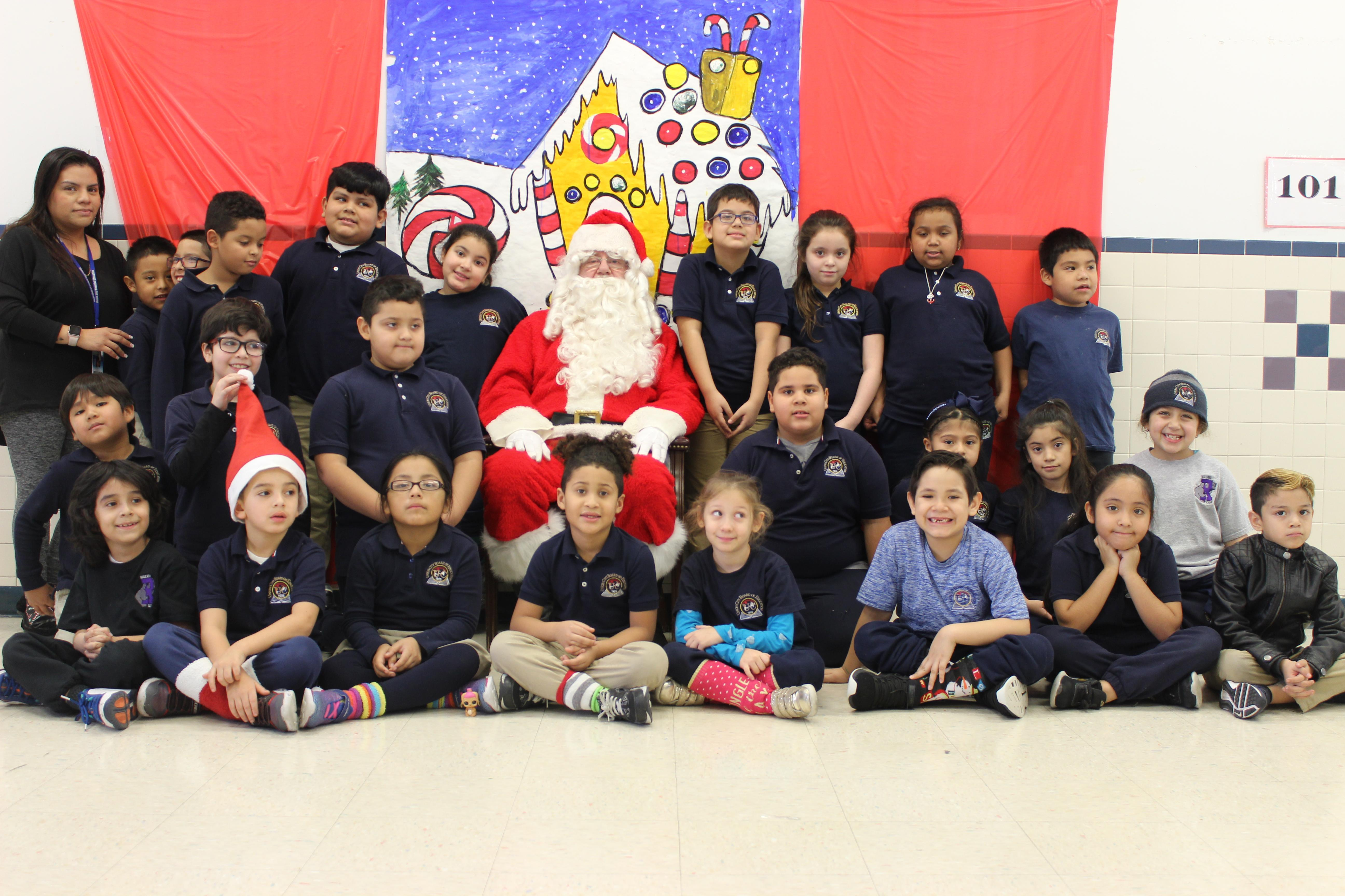 4th grade class with teacher and aides posing with santa