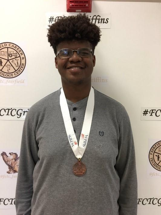 Student smiling with medal