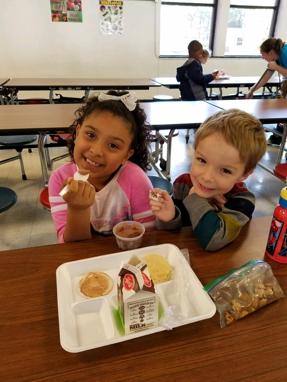 Lunch room picture of a boy and a girl eating