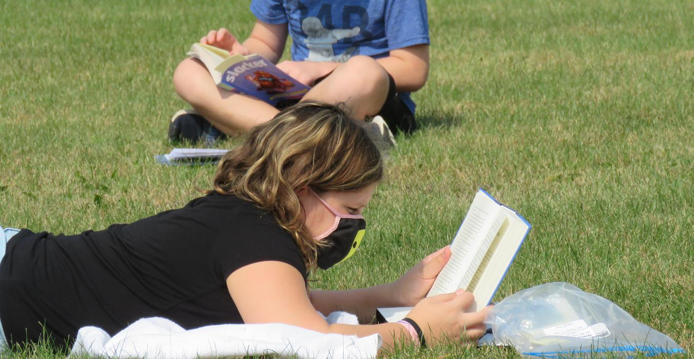 Students enjoy reading time outside.