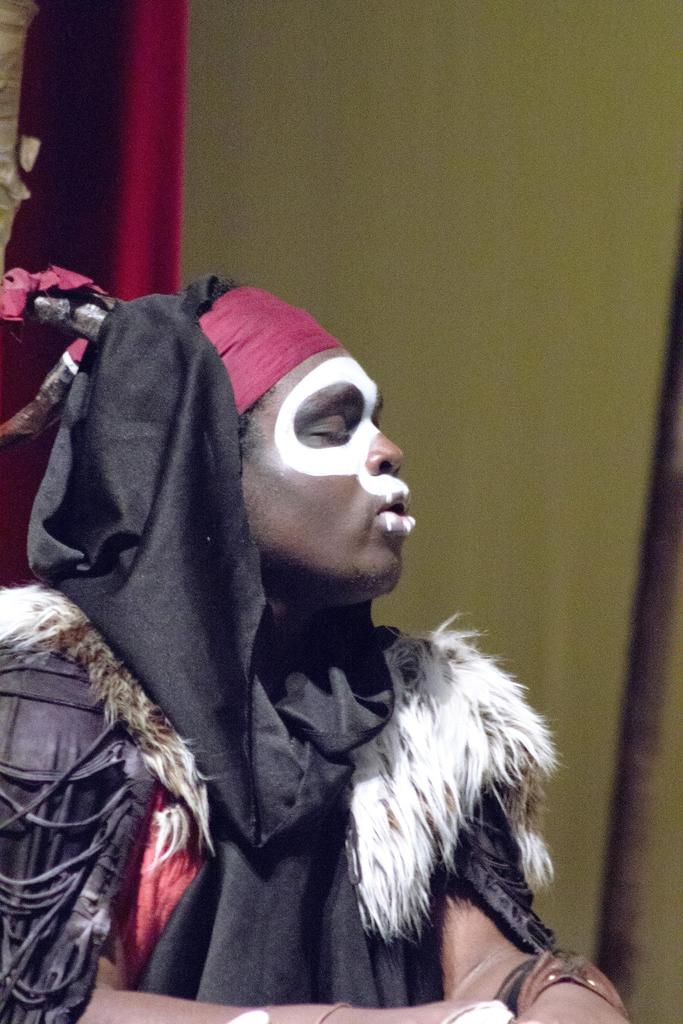 A close-up of Marck Hens Jules, his face painted, as he plays Papa Ge, Demon of Death