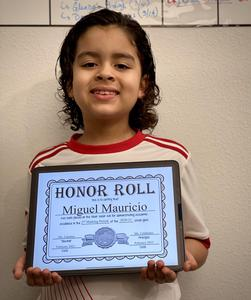 Miguel holding honor roll certificate