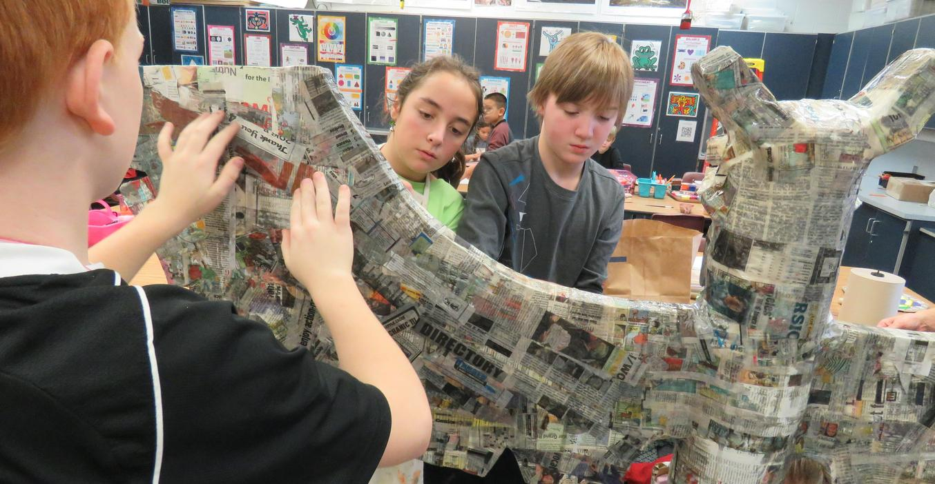 Page students work on a papier mache project in art class.
