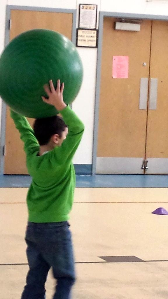 child in the gym, a boy, with his hands above his head with a large green ball over his head to throw it to another child