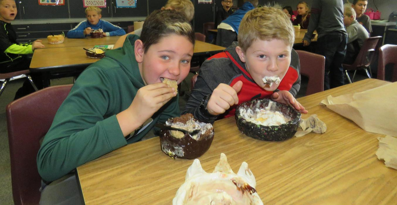 Students enjoy ice cream sundaes served in their handmade bowls.