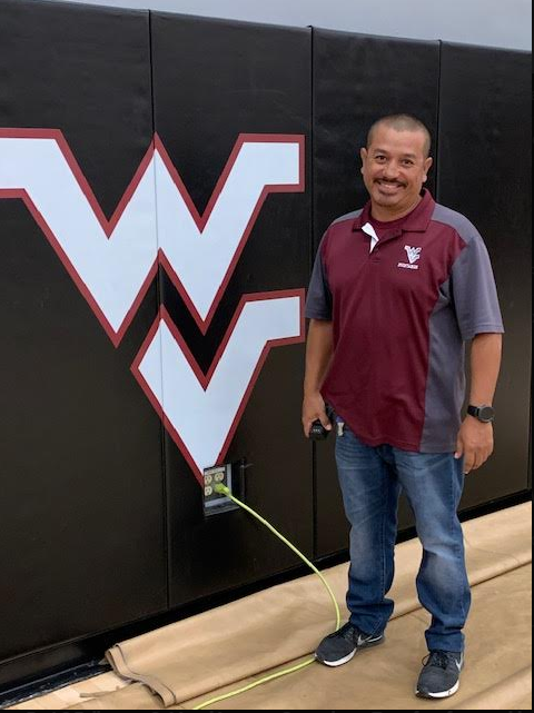 Juan Sandoval standing in front of a West Valley sign.