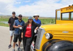 A team poses for a group shot with an antique school bus at RedHawk golf course.