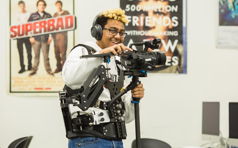 Student adjusting camera equipment in class.
