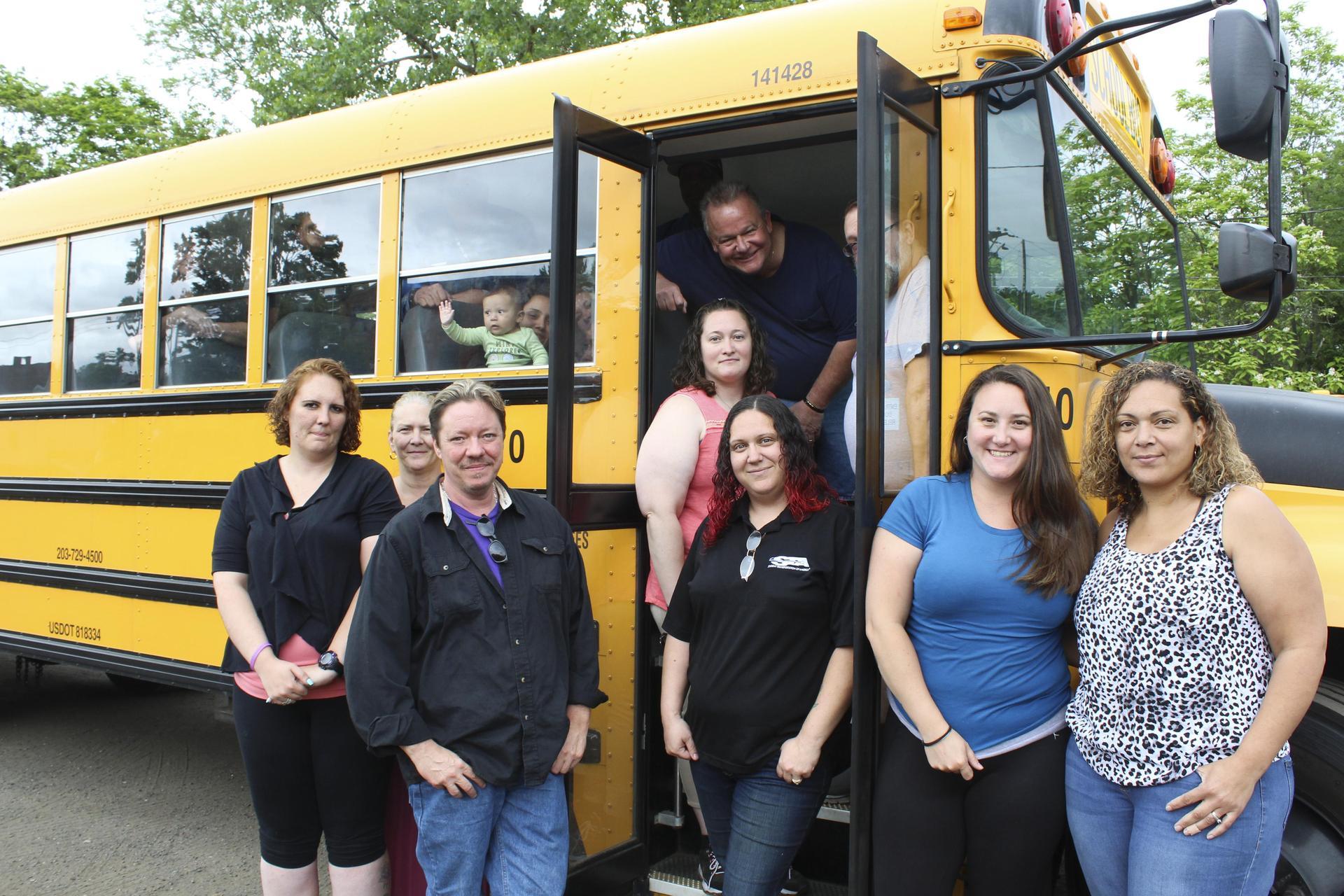 Bus drivers posing in door of bus