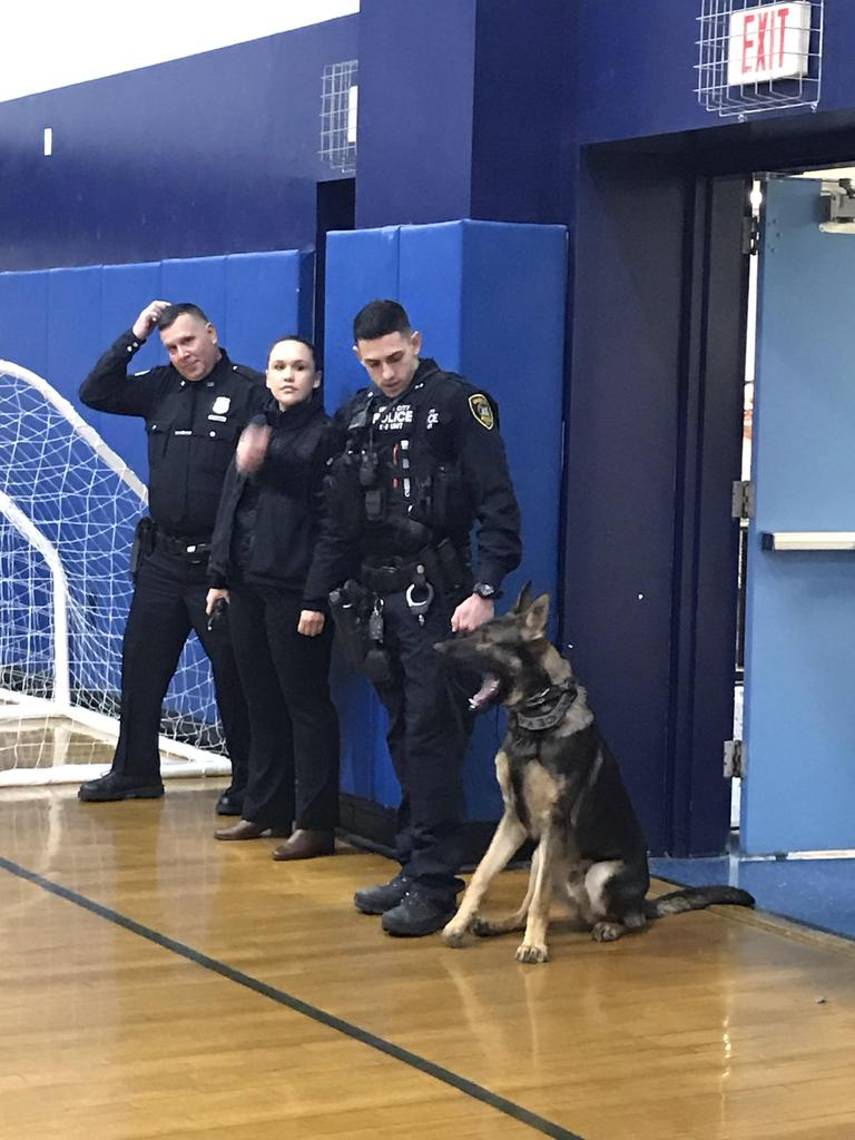 three policie officers stadning in the gym along side the dog that is yawning