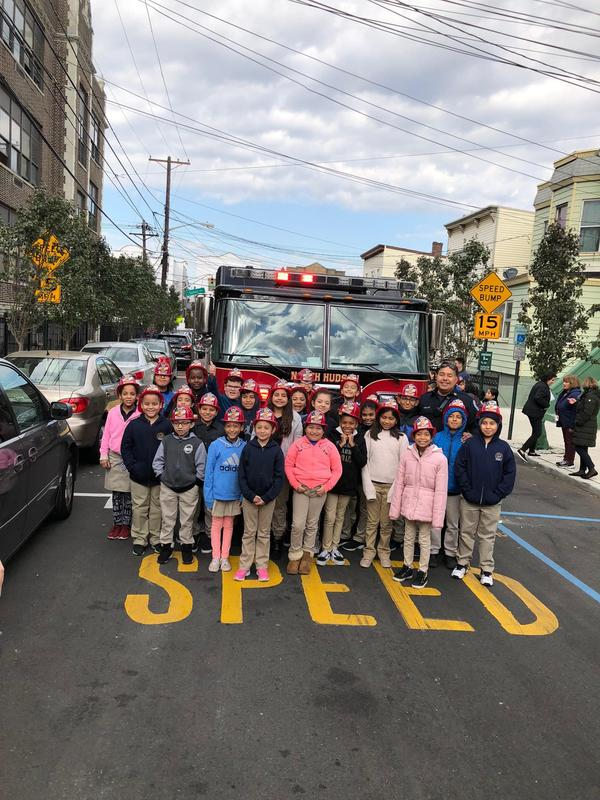 class proudly stands in front of the fire truck