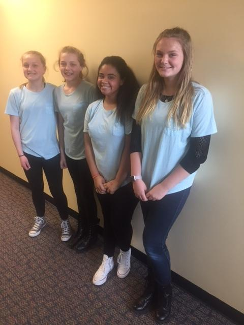 four girls in blue shirts smile