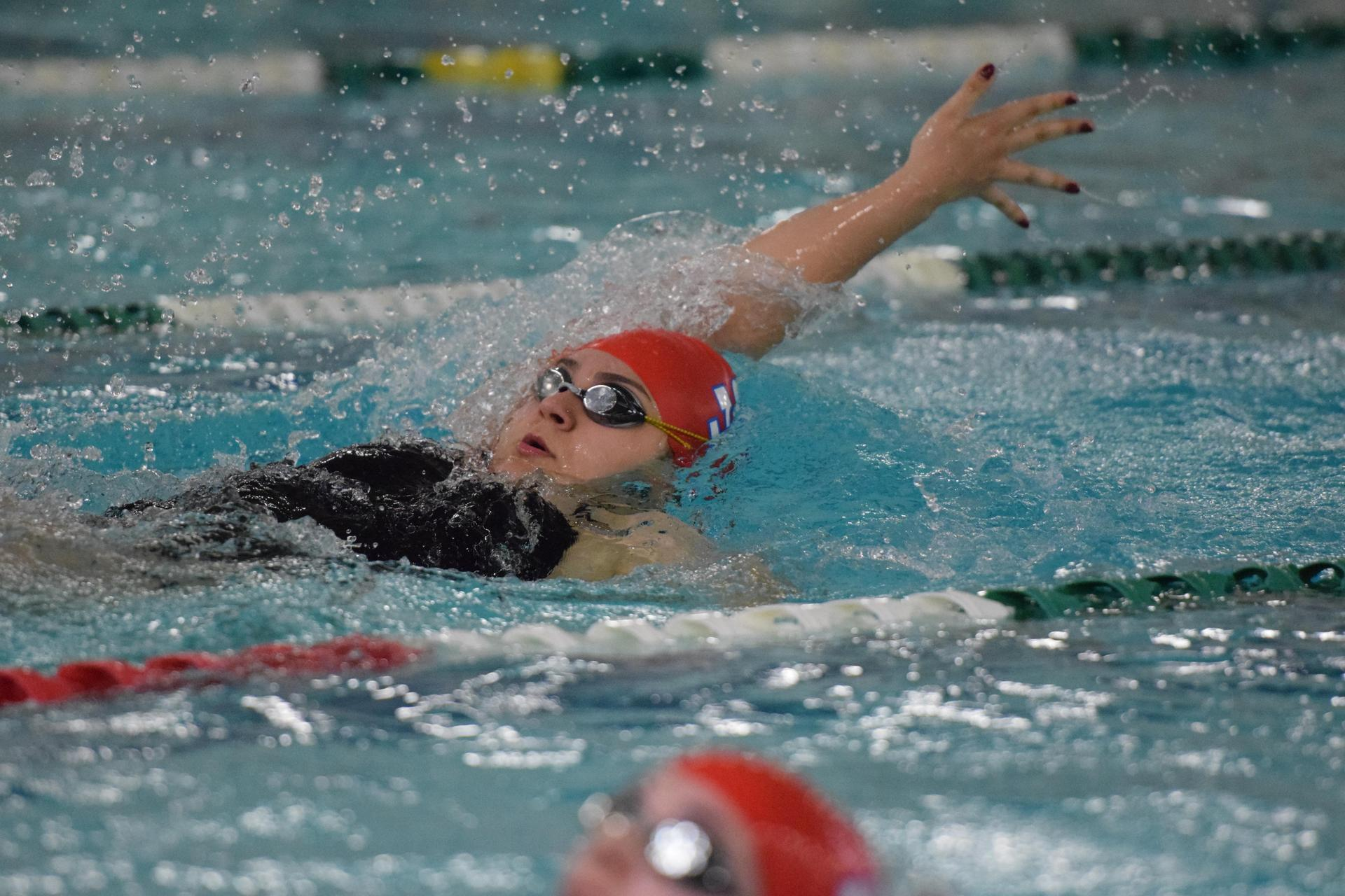 female swimming competes in backstroke