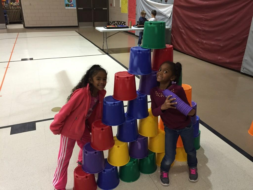 two girls pose with stack of pails they created