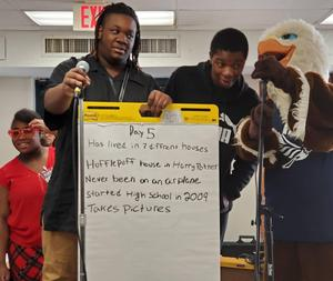 Three students and an Eagle Mascot gather around a large post-it with writing on it