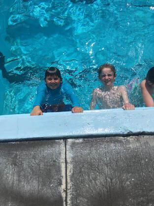 Three Children swimming in an outdoor pool