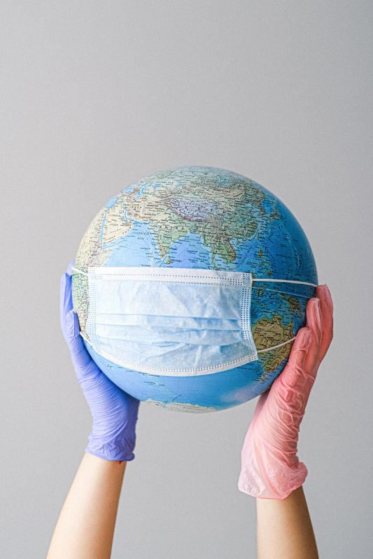 hands-with-latex-gloves-holding-a-globe-with-a-face-mask-4167544.jpg