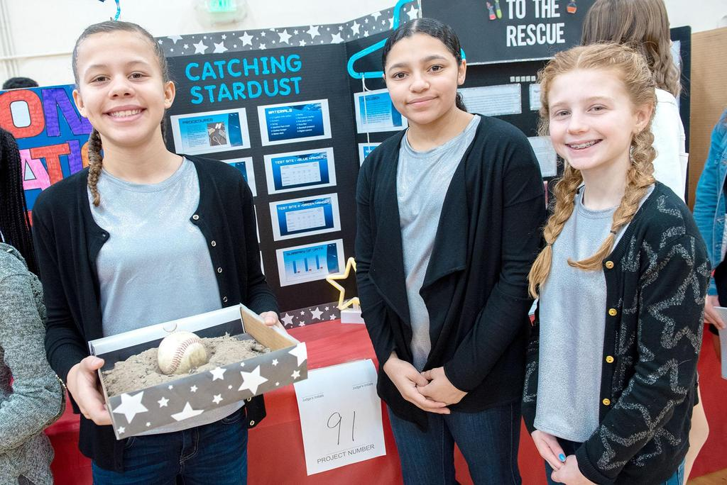 Three students stand in front of their project, one of whom is holding a box filled with dust and a baseball