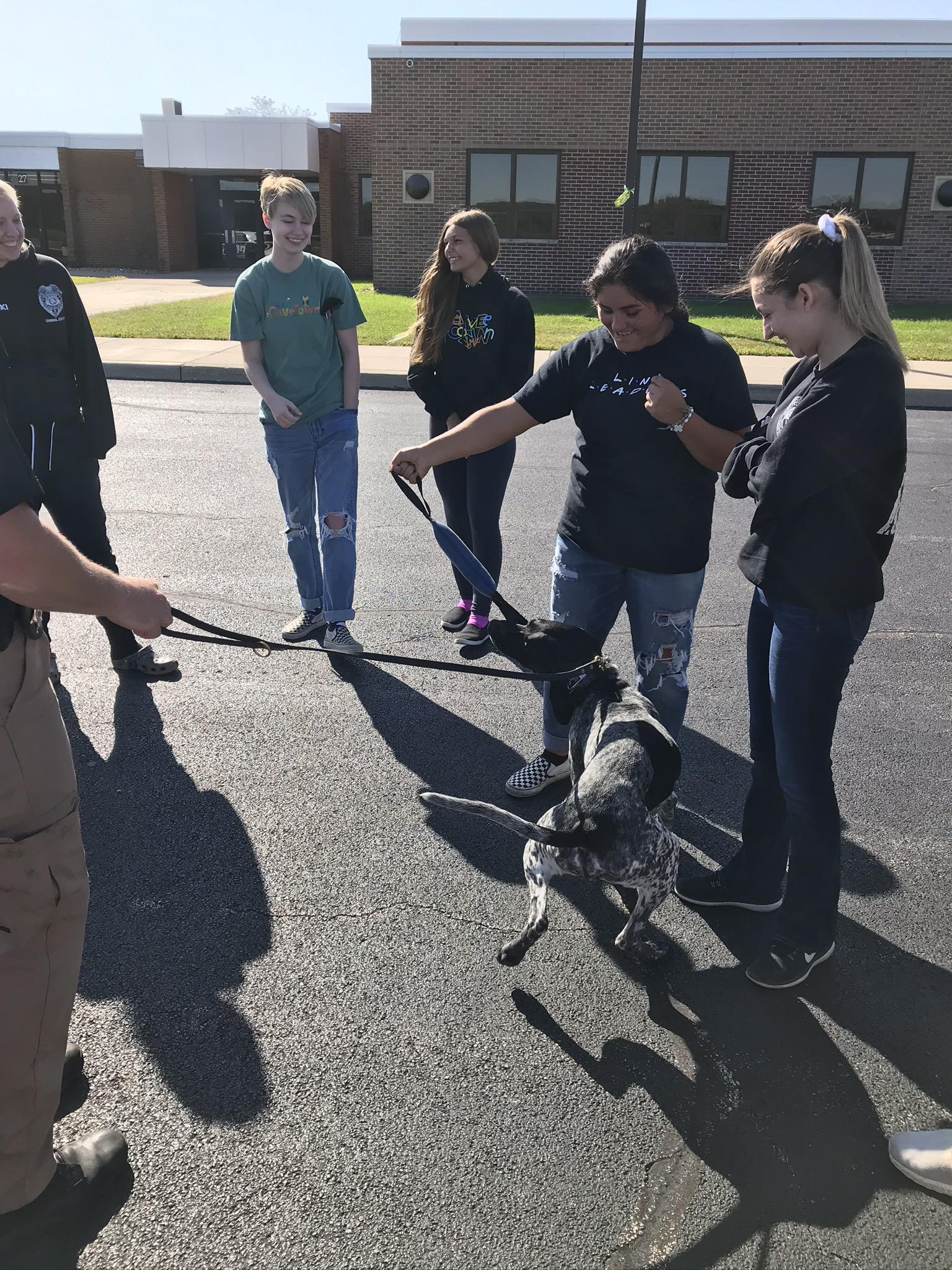 Student playing with Police K-9 Rookie