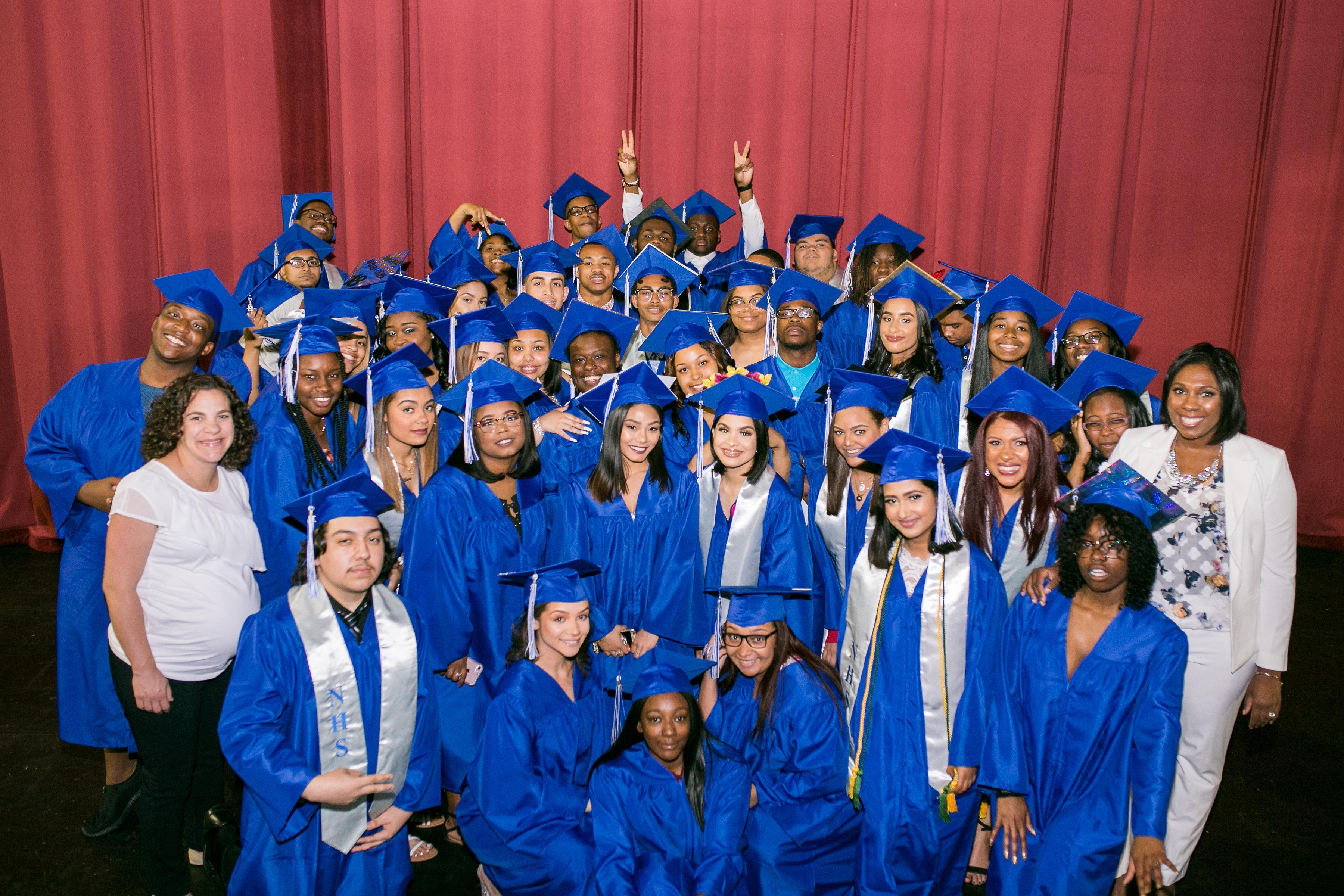 Chief of School and Principal take a picture with a senior class at their graduation