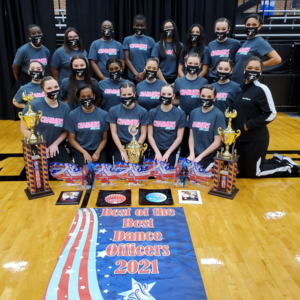 group of teen girls in matching shirts pose together with trophies and awards