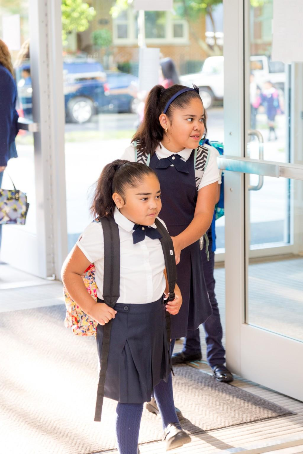 Two young female students entering the school