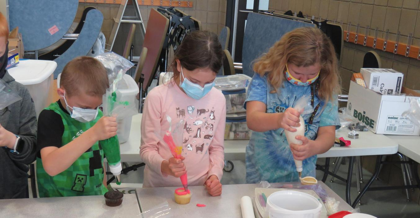 Students use piping bags to frost their cupcakes.