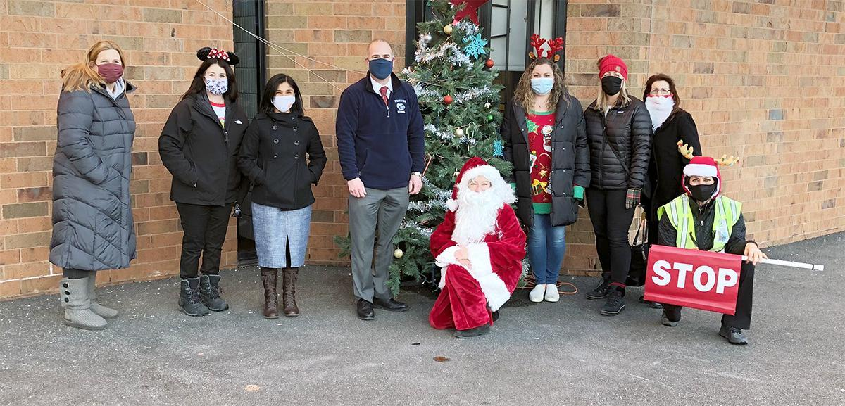 Adults standing outside, in front of a Christmas tree